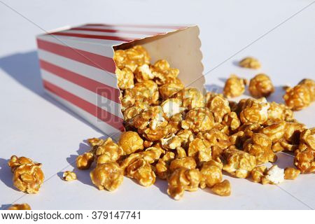 Popcorn. Caramel flavored Pop Corn in a Red and White Striped Paper Container.  Room for text. Clipping Path. Caramel Popcorn is enjoyed by happy people world wide.