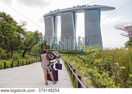 Singapore, Singapore - January 17, 2013. Woman Looks On Marina Bay Sands Hotel Through Binoculars Fr