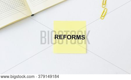 The Word Of Reforms On Paper On Office Table. Economy Reforms Concept