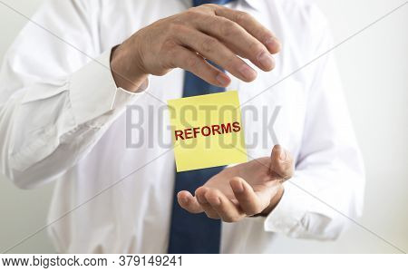The Word Of Reform On Paper In Businessman Hand. Economy Reforms Concept