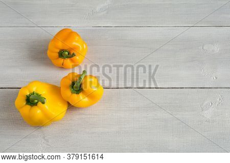 Shaped Yellow Bell Peppers On The Wooden White Background. Misshapen Produce, Food Waste Problem Con