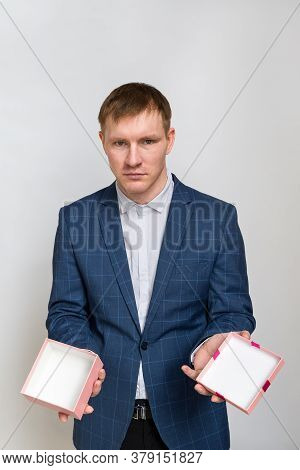 Portrait Of A Young Man With Red Hair In Casual Clothing Jacket And Shirt. Hes Holding An Empty Gift