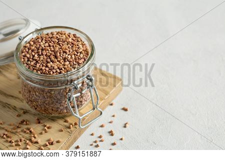 Buckwheat Uncooked Grains In Glass Jar On The Wooden Cutting Board On Gray Background. Healthy, Diet