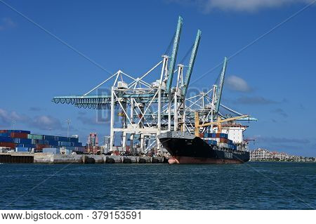 Miami, Florida 05-30-2019 Container Ship Loads Cargo Containers Under Gantry Cranes Of Port Miami On