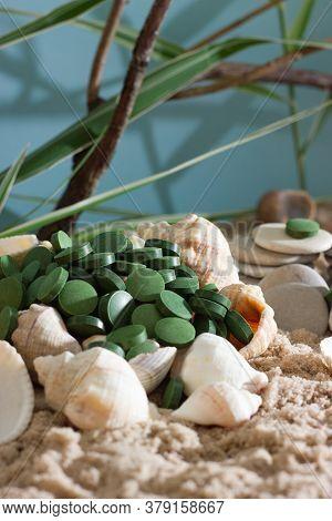 Superfood : Spirulina Or Chlorella Tablets Among Shells, Rocks And Sand. Vegan Food.