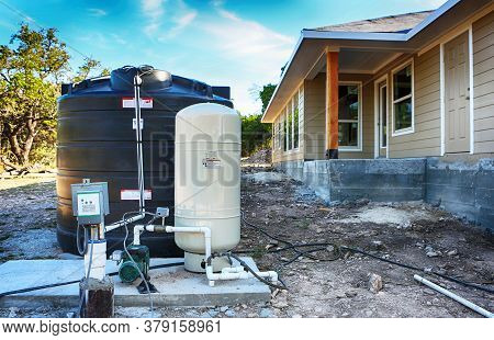 Deep Water Well Set Up In Front Of Home Construction.  Drilled Draw Well With Pressure Switch And St