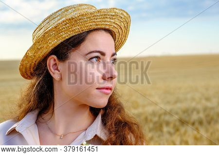 Close Up Portrait Of A Smiling Woman In Straw Hat In Wheat Field At Morning.