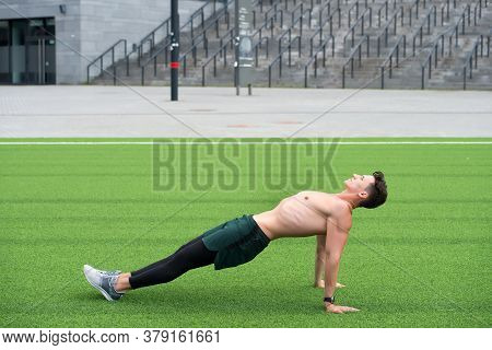 Sporty Man Making Back Plank Exercise. Guy In Reverse Plank Exercise. Yoga Fitness Man Stretching Bo