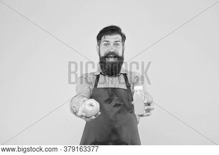 Man Bearded Chef Hold Organic Natural Tomato And Bottle Yellow Background. Vegetarian Nutrition. Smo