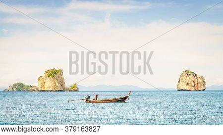 Krabi, Thailand, November 9, 2017: Thai long tail fishing boat in the Andaman Sea with islands and Krabi coastline on the horizon