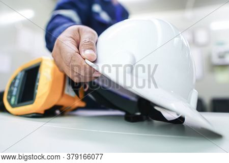 The Engineer Picks Up The White Helmet Placed On The Office Desk With A Blurred Background.