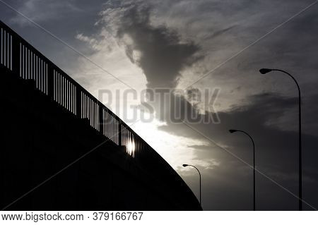 Silhouette Of Bridge And Lampposts At Sunset, In The City. With The Sky With Clouds.