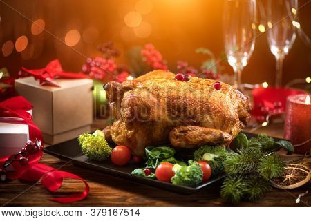 Christmas Dinner. Roasted chicken. Winter Holiday table served, decorated with candles. Roast turkey over blinking background with Christmas tree, table setting. Xmas