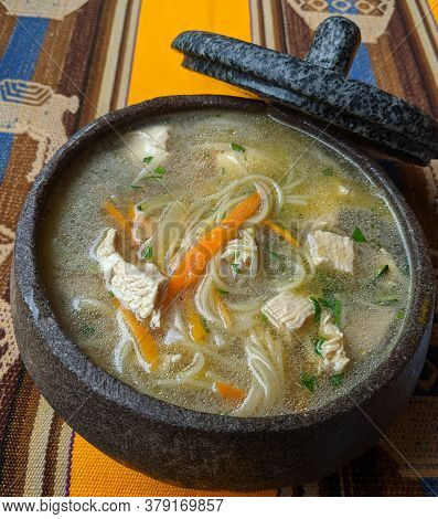 Black Stone Crock Of Traditional Andean Chicken Soup On Bright Tablecloth