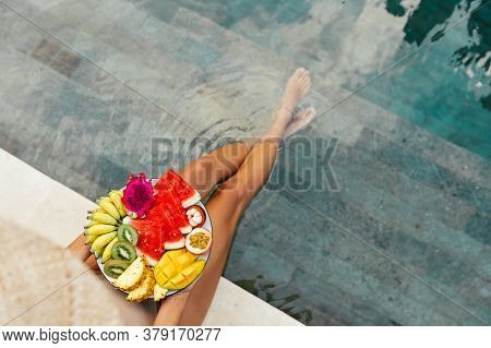 Girl Relaxing And Eating Fruit Plate By The Hotel Pool. Exotic Summer Diet. Photo Of Legs With Healt