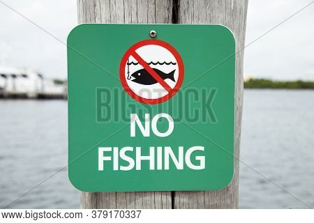 Sign In Front Of Some Water Asking People Not To Fish. No Fishing Beyond This Point.