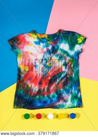T-shirt In Tie Dye Style And Paint On A Three-color Background. White Clothes Painted By Hand. Flat