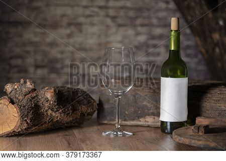 Close Up Of An Empty Glass Surrounded By A Bottle Of Wine And Chunks Of Wood On A Wooden Table On An