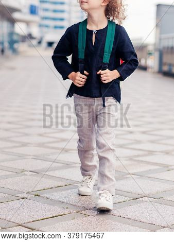 A Schoolboy Boy In Light Pants And A Dark Shirt Walks Down The Street With A Backpack On His Back