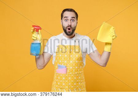 Shocked Young Man Househusband In Apron Rubber Gloves Hold Spray With Washing Cleanser, Cleaning Rag