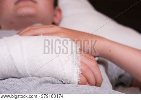 A Lying Boy With Broken Arm In Plaster Case, Hand Injury Because Of Accident, Forearm Bones Fracture