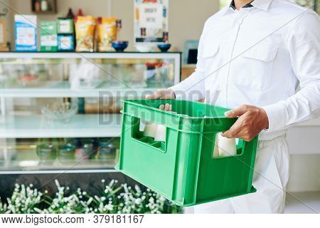 Cropped Image Of Delivery Man In White Uniform Carrying Plastic Milk Crate To The Grocery Store