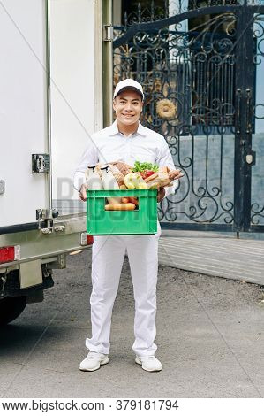 Portrait Of Handsome Young Vietnamese Courier Holding Plastic Crate With Milk Bottles, Fresh Bread A