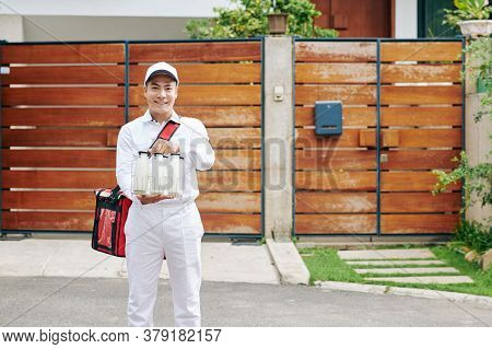 Positive Young Asian Delivery Man In White Unifrom Holding Wire Milk Crate With