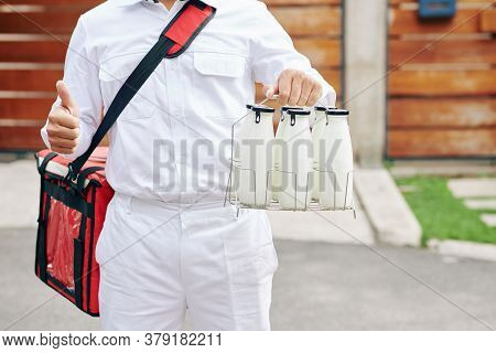 Cropped Image Of Delivery Man Holding Wire Crate With Glass Milk Bottles And Showing Thumbs-up