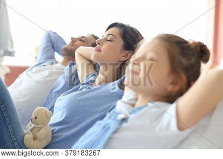 Relaxed Young Family Resting And Dreaming About New Home On Comfortable Sofa Together At Home, Happy