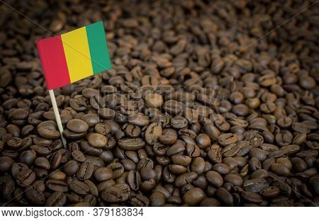 Guinea Flag Sticking In Roasted Coffee Beans. The Concept Of Export And Import Of Coffee