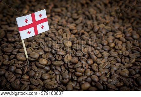 Georgia Flag Sticking In Roasted Coffee Beans. The Concept Of Export And Import Of Coffee