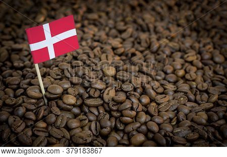 Denmark Flag Sticking In Roasted Coffee Beans. The Concept Of Export And Import Of Coffee