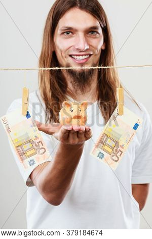 Savings Concept. Young Handsome Long Haired Joful Man Holding Piggybank Moneybox Around Banknotes Ca