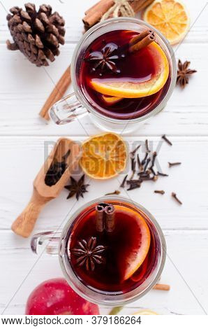 Two Glasses Of Hot Red Mulled Wine Or Gluhwein With Orange, Cinnamon Sticks And Anise On White Woode