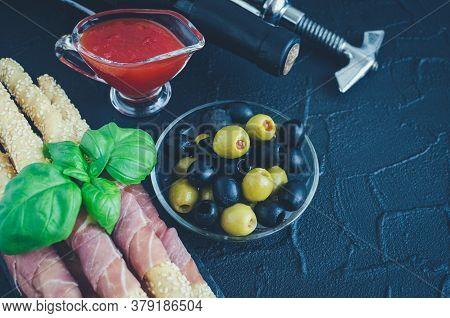 Bottle Of Wine With Antipasti On Dark Stone Background. Grissini Breadsticks With Prosciutto Ham, Ba