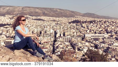 Young Woman Is On Background Of Urban Landscape Of Athens, Greece, Europe. Adult Pretty Girl Tourist