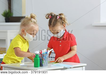Children In The Classroom In Medical Masks Draw Markers In A Bright Classroom, On The Table Is A San