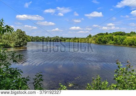 Beautiful Natural Landscape Of A Rural Pond With Lush Green Nature In A Hilly Area. Spring-summer Pa