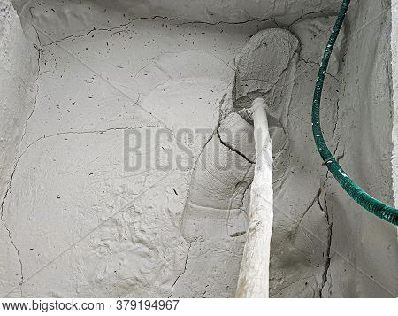 Top View Of Limestone Paste In Large Quantity Taking Out With The Help Of Iron Spade From The Well.