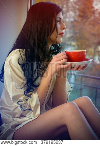 Young Beautiful Dreaming Brunette Woman Drinking Cup Of Coffee Wearing Lingerie Sitting Home By The