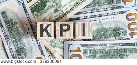 Concept Words Kpi On Wooden Blocks On A Beautiful Background From Dollar Bills.