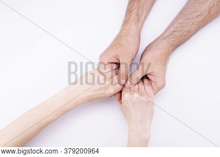 The Womans Hands In The Mans Hands Lie On A White Background. Man And Woman Holding Hands, Relations