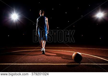 Basketball. A Teenager In Blue Sportswear Walks Away From A Basketball Lying On The Floor On Sport C