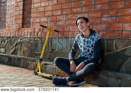 A Teenage Boy Sits On The Sidewalk Next To A Scooter, And Sticks Out His Tongue. Brick Wall In The B