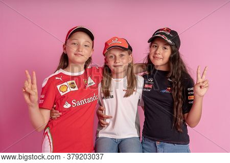Three Little Girls In Clothes With Logos Of Formula One Race Sponsors On A Pink Background. Children