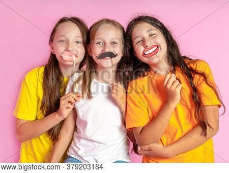 Happy Children Hold Fake Mustache And Lips On A Pink Background. Beauty Salon. Hair Design Salon. Sa