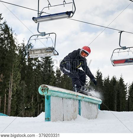 Male Snowboarder In Helmet Riding Snowboard Under Cloudy Sky And Ski Lifts. Man In Black Winter Suit