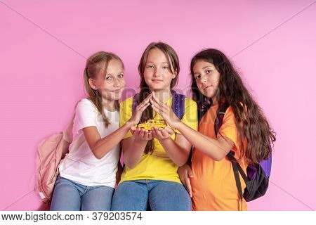 Three Girls Schoolgirls Are Holding A Toy School Bus In Their Hands. The Concept Of The Safety Of Ch