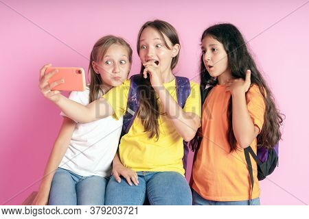 Three Teen Girls Smiling And Shoots A Video On A Pink Background. Selfies.